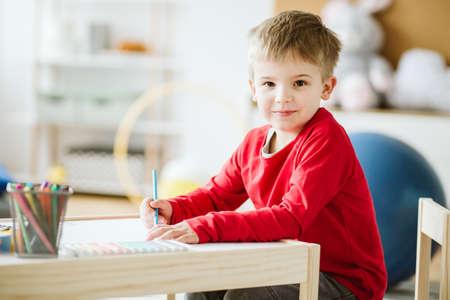 Netter kleiner Junge mit rotem Pullover, der an einem kleinen Holztisch sitzt