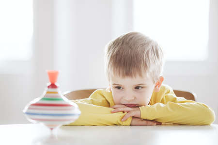 Thoughtful little boy sits at the table and looks at the spinning top Archivio Fotografico