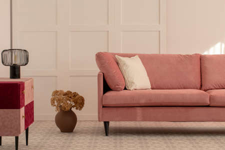 Flowers in earthenware vase next to pastel pink couch with white pillow