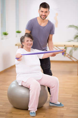 Elderly lady siting on the exercise ball during physiotherapy with her young instructor Stock Photo