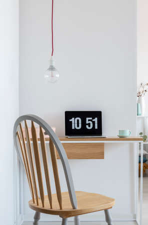 Clock screensaver on a laptop in bright home office interior with wooden chair, simple desk and bare light-bulb. Real photo