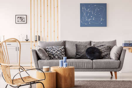 Korbstuhl neben Holzblock-Couchtisch im modischen Wohnzimmer-Interieur