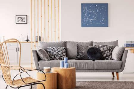 Rieten stoel naast houten blok salontafel in trendy woonkamer interieur living