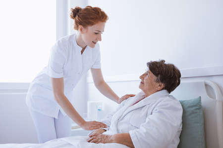 Young beautiful female doctor and senior patient at hospital