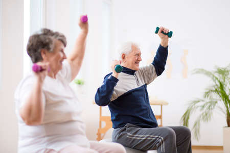 Elderly man exercising with his friend during pilates for seniors