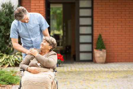 Male nurse helping happy elderly woman in the wheelchair in front of house