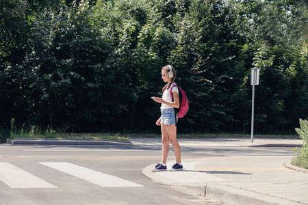 Jolie écolière adolescente avec un casque et un téléphone portable sur le passage pour piétons Banque d'images