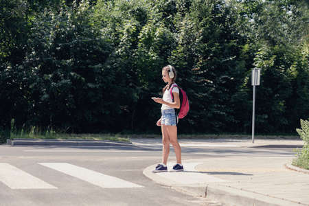Pretty teenage schoolgirl with headphones and mobile phone on pedestrian crossing Фото со стока