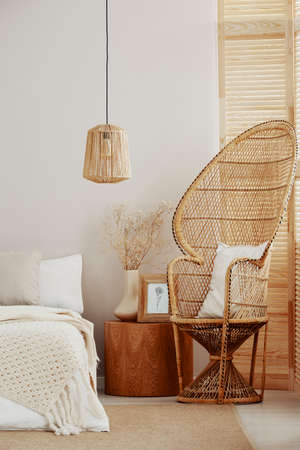 White and bright bedroom interior with wicker peacock chair with white pillow, rattan lamp and wooden nightstand with frame with poster and vase with flowers