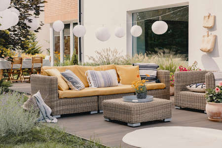Echtes Foto eines Rattan-Gartenmöbel-Sets mit Lampen und Tisch im Hintergrund