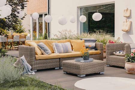 Vraie photo d'un ensemble de meubles de jardin en rotin avec lampes et table en arrière-plan