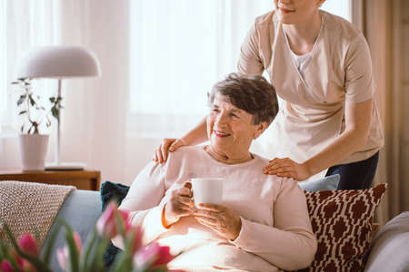 Smiling senior woman drinking tea with her caregiver standing behind her