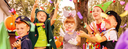 Panoramic view of animator and kids enjoying confetti rain during birthday dressing up party in the garden Banque d'images - 122007275