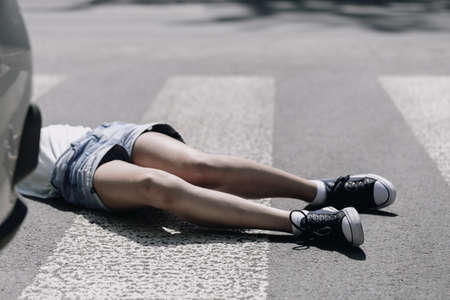 Teenage kid lying on the street after terrible car crash on pedestrian crossing