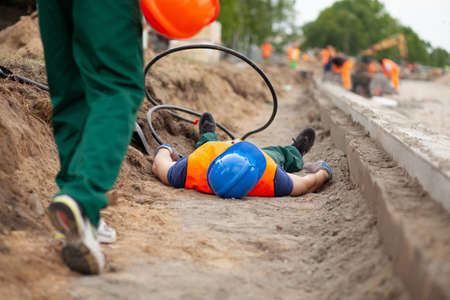 Road construction worker lying on the ground after terrible accident