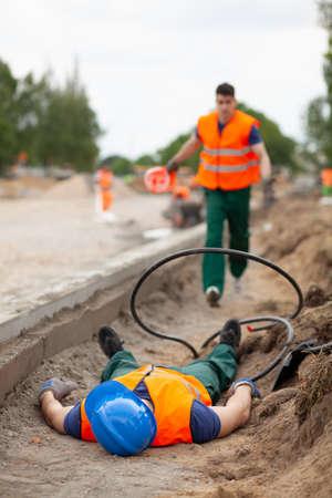 Wypadek podczas budowy drogi, ranny pracownik leżący na ziemi Zdjęcie Seryjne