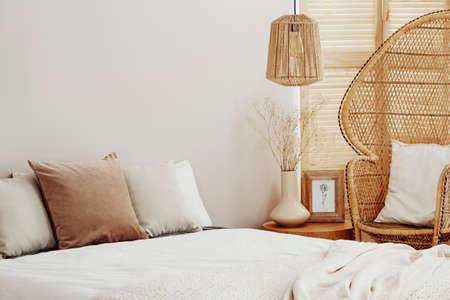 Intérieur de chambre blanc et lumineux avec chaise paon en osier et lampe en rotin