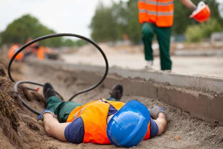 Primo piano di un operaio edile ferito sdraiato a terra