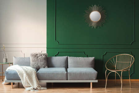 Golden sun shape like mirror on green wall of living room interior with scandinavian sofa with pillows