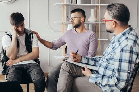 Young man in glasses comforting his depressed friend during meeting with counselor Imagens