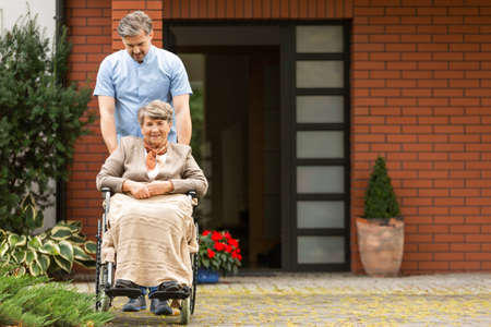 Smiling senior woman in the wheelchair supported by caregiver in front of house 스톡 콘텐츠