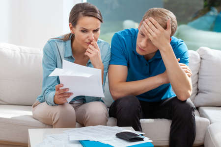 Stressed married couple looking frustrated, having no money to pay off their debts, managing family budget together