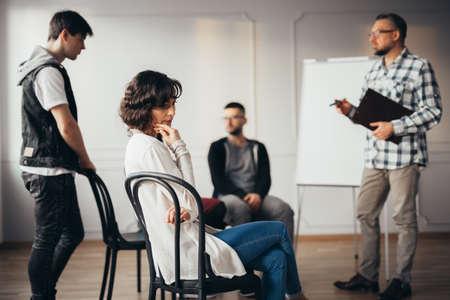 Mujer triste perdida en sus pensamientos durante la reunión con el asesor social