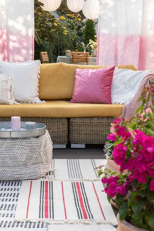 Gros plan de fleurs roses sur une terrasse avec un canapé en osier et des oreillers en arrière-plan. Vrai photo