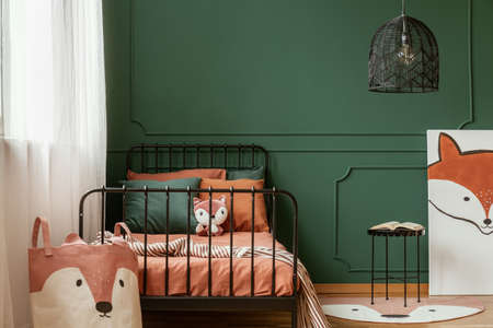 Fox-themed kid bedroom interior with molding on green wall and orange sheets on the bed. Real photo