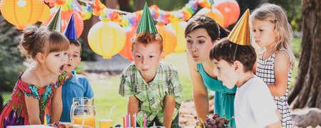 Vue panoramique d'un garçon roux, d'un animateur de fête et d'écoliers soufflant des bougies sur un gâteau d'anniversaire lors d'une garden-party pour les enfants