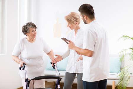 전문 여성 의사와 남성 간호사와 함께 물리 치료를 받는 동안 보행기가 있는 회색 노부인