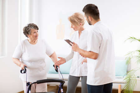 Grey senior lady with walker during physiotherapy with professional female doctor and male nurse