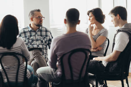 Woman talking to professional psychotherapist in support group for ACOA
