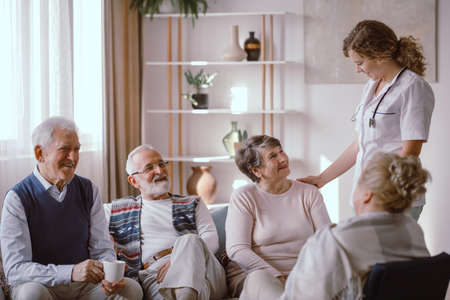 Smiling seniors talking with nurse in the retirement home