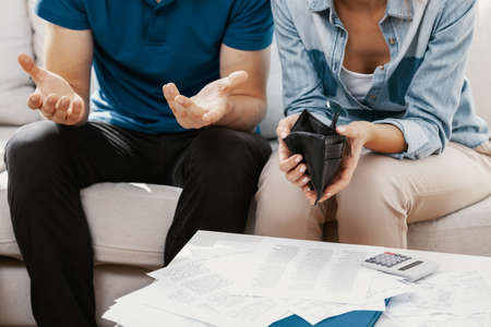 Young married couple sitting in living room with empty wall and pile of bills Banco de Imagens