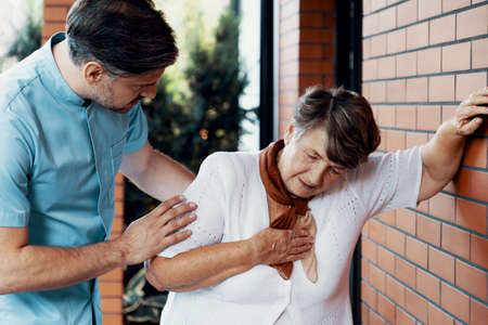 Male nurse helping sick elderly woman with chest pain