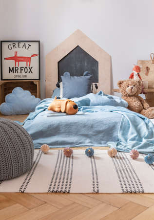 Pouf on striped rug in child's bedroom interior with teddy bear next to blue bed and poster. Real photo