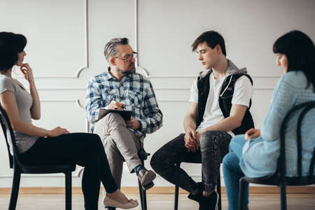 Group therapy session with psychologist and depressed man and woman Stock Photo