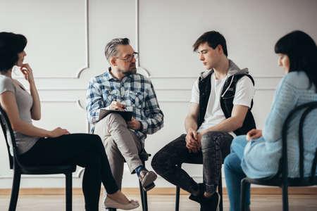 Sesión de terapia grupal con psicólogo y hombre y mujer deprimidos