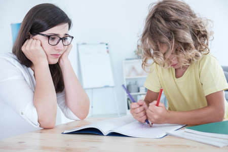 Kid with adhd doing homework during extra-curricular classes with worried teacher Stock Photo