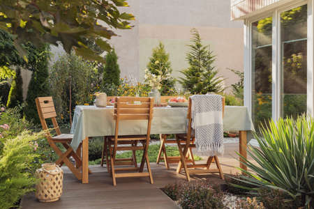 Lantern next to wooden chairs and table on the terrace of house with plants and blanket. Real photo