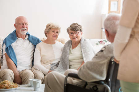 Group of senior friends sitting together in common living room of nursing home