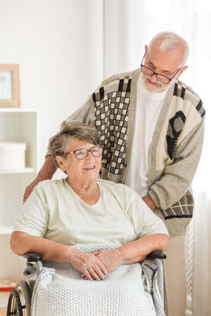 Senior woman on wheelchair with elderly friend behind her