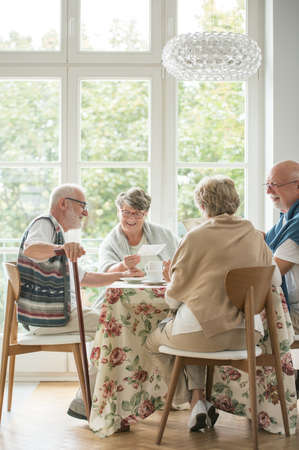 Senior friends spending time together by drinking tea and enjoying photos