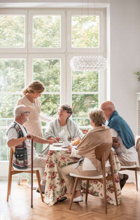 Elderly friends spending time together by drinking tea and enjoying photos in common dining room of nursing home