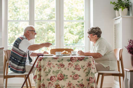 Senior couple sitting together at table drinking tea and eating cake Stockfoto