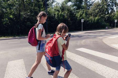 Schooljongen met rugzak en zijn tienerzus die mobiele telefoons gebruikt op zebrapad Stockfoto
