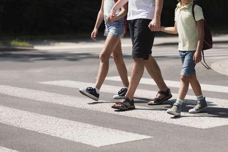 Vader hand in hand met zijn kinderen op zebrapad