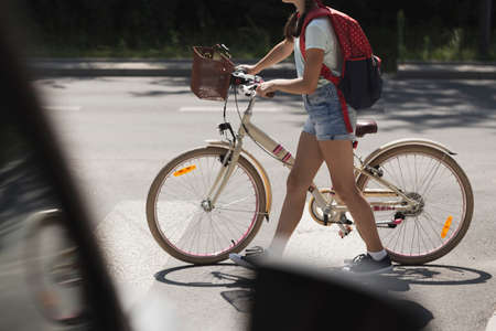 Schoolgirl with backpack and bike crossing street in front of a car Stockfoto