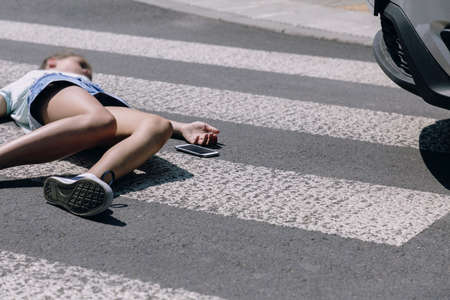 Teenage girl with mobile phone lying on the street after terrible car crash on pedestrian crossing